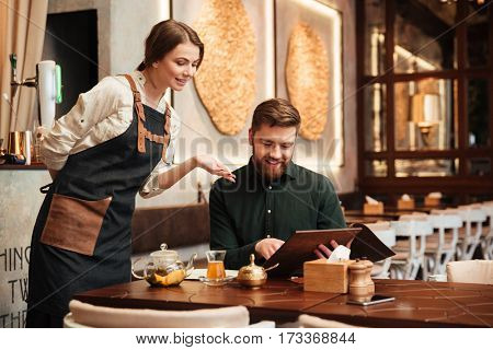 Image of attractive bearded young man sitting in cafe. Looking at menu list.