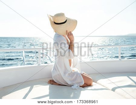 Side view photo of young amazing woman wearing hat sitting on the yacht