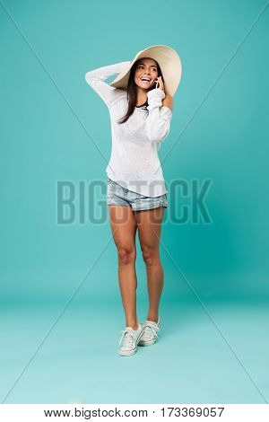 Vertical image of happy woman in beachwear which talking on phone and looking away. Isolated turquoise background