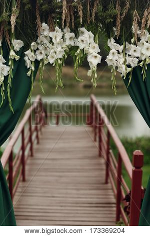 Beautiful Stylish Wedding Aisle Pathway With White Floral Garland Hanging From Arc With Green Fashio