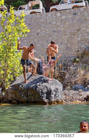 Kemer Antalya Turkey - august 26 2014: Holidaymakers are having fun near the mountain river in a canyon Kuzdere two vacationers thrown into the water his companion.