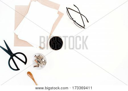 Top view office table desk. Workspace with coffee craft envelope scissors paper blank on white background. Flat lay.