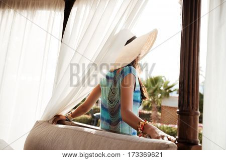 Back view of Young Brunette woman in beachwear which posing near the alcove