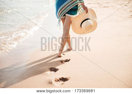 Cropped image of woman walking on the sand near the sea