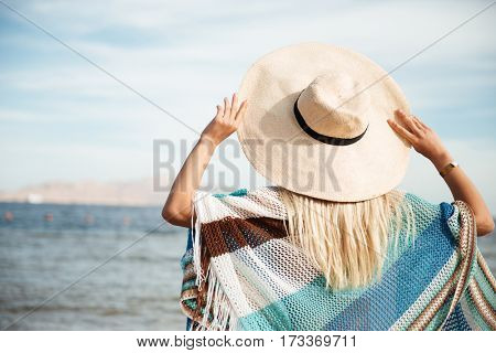 Back view of woman in beachwear and hat which standing on the beach and holding her hat