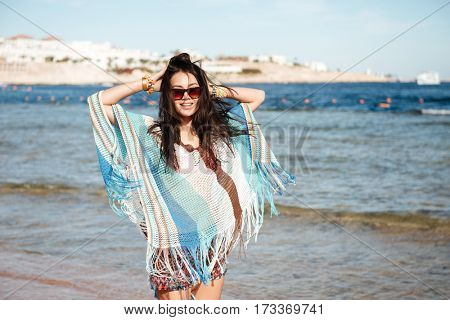 Woman in beachwear and sunglasses which standing on the beach near the sea