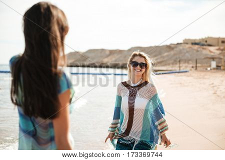 View from back of girl with her friend in sunglasses on the beach near the sea