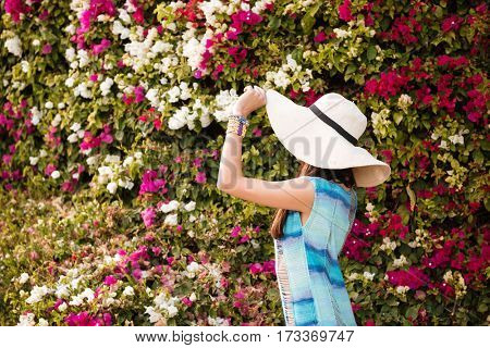 Side view of woman in hat and beachwear which posing near the flower bush