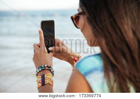 Back view of young woman in beachwear which making photo on phone and standing on the beach