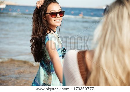 View from back of girl with her friend on the beach near the sea
