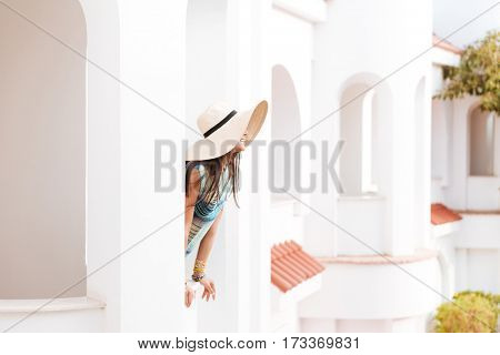 Side view of woman in beachwear which standing on balcony and looking away