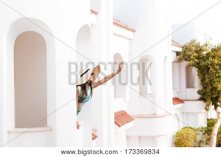 Side view of Young woman in beachwear which standing on balcony and waving away