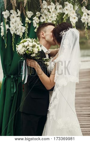 Happy Newlywed Couple Hugging Under White Flowers Aisle Arch, Handsome Groom Kissing Beautiful Brune