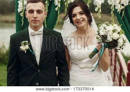 Gorgeous Bride And Stylish Groom Hugging And Smiling On Aisle At Lake At Wedding Outdoor Reception A