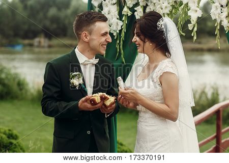 Happy Newlywed Couple Breaking Bread At Wedding Ceremony, Handsome Groom And Smiling Bride Eating Br