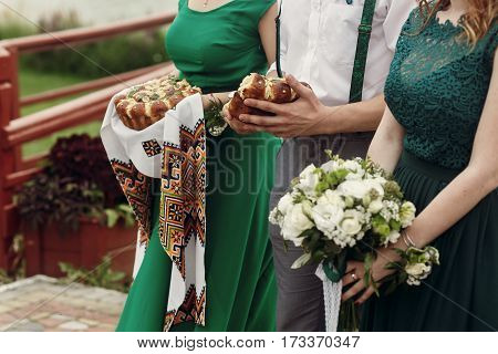 Beautiful Bridesmaids In Stylish Green Dress With White Flowers Bouquet And Holding Traditional Brea