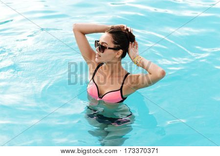 Brunette Woman in swimsuit and sunglasses which swimming in the pool and looking away