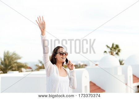 Brunette woman in white clothes which talking on phone and waving away