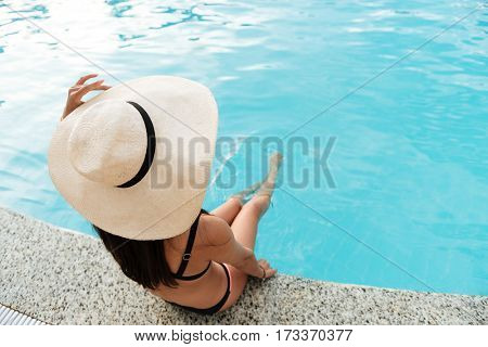 View from above of Woman in swimsuit and hat which sitting near the pool and holding her legs in water. Back view