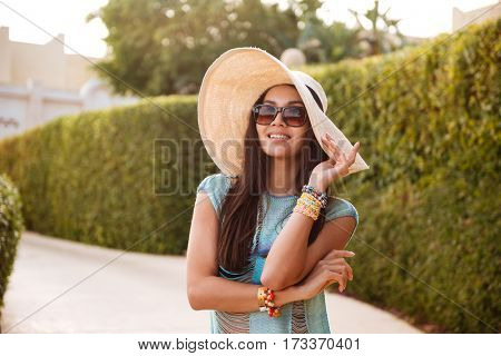 Close-up view of Brunette Woman in beachwear which posing near the bush and looking at camera
