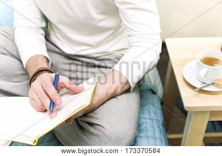 Man sitting on a bed with coffee and planning his day activity closeup cropped shot