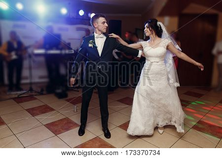 Romantic Newlywed Couple Dancing, Handsome Groom And Beautiful Happy Bride First Dance While Holding