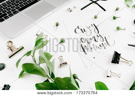 White office desk workspace with quote Enjoy Every Moment green leaves and office supplies. Laptop scissors glasses on white background. Top view.