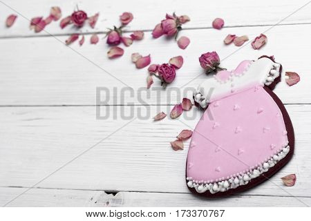 Cookies With Glaze In The Form Of Dress With Flying Petals Of Dried Roses. On White Wooden Surface.