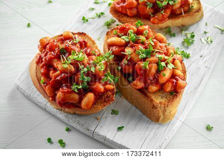 Beans fried in tomato sauce on toasted bread with cross salad sprinkle.