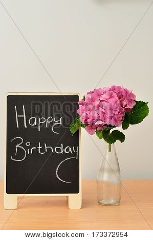 A blackboard with a happy birthday message and hydrangeas in a bottle next to it