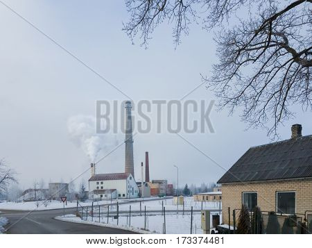 Small town landscape with smoking chimney on background. Small thermal power station.