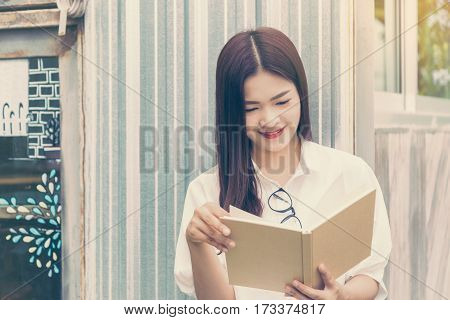 happy asian woman with eyeglasses enjoy reading outdoor in her garden with warm evening sunlight and flare vintage retro color style