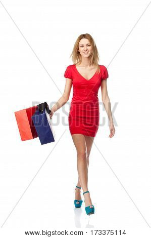 Young blonde woman with shopping bags. Isolated over white background