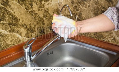 Man hand holding a sponge to wash dishes with foam at the kitchen