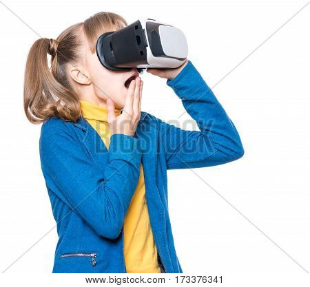 Amazed little girl wearing virtual reality goggles watching movies or playing video games, on white. Surprised kid looking in VR glasses. Emotional portrait of child experiencing 3D gadget technology.