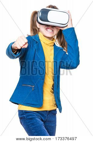 Anger little girl wearing virtual reality goggles watching movies or playing video games, isolated on white background. Emotional portrait of upset child looking in VR glasses and showing fist.