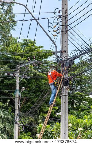 Worker working to install electric line by scaffolding on pickup truck at Bangkok Thailand.