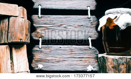 Tied honey jar on wood stump. Other stumps in stack. Triple wood sign on the background. Isolated over black