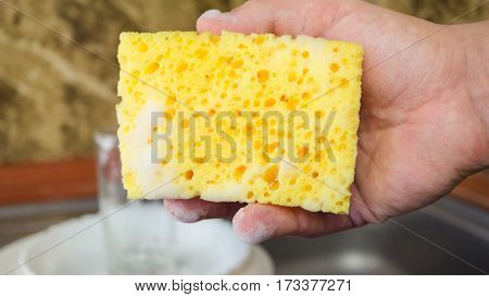 Man for hand holding a sponge to wash dishes with foam at the kitchen close up