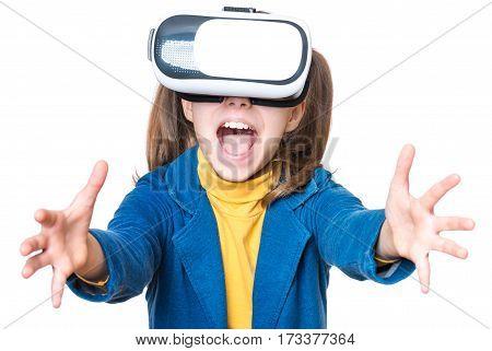 Happy little girl wearing virtual reality goggles watching movies or playing video games, isolated on white background. Cheerful smiling child looking in VR glasses and gesturing with his hands.