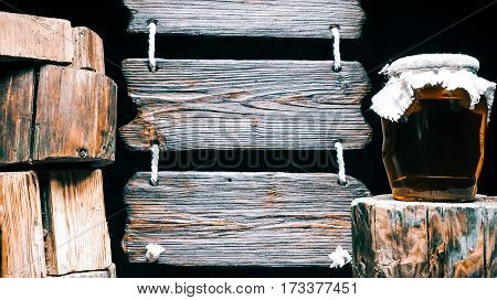 Honey jar on wood stump. Other stumps in stack. Triple wood sign on the background. Isolated over black