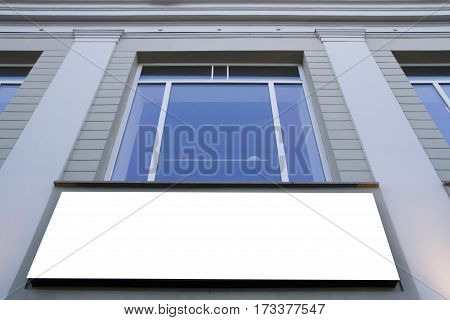 Mock up. Blank billboard outdoors, outdoor advertising, public information board on the wall under window. Low angle view