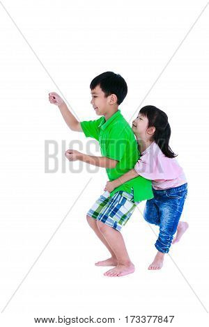 Asian sister standing and hugging his brother smiling happily isolated on white background. Concept about loving and bonding of sibling. Playful boy driving a train or car. Children role playing. Studio shot.
