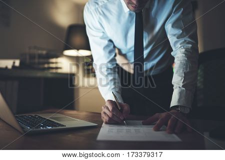 Serious businessman signing contract at office working at night overtime