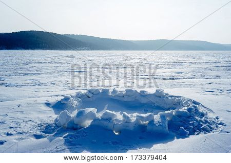 Hole for winter fishing on the lake in the background of snowy mountains