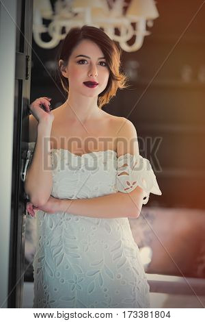Beautiful Young Woman Standing Near The Door In The Light Luxury Room