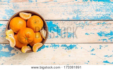 Mandarins in a bowl on wooden table.top view.