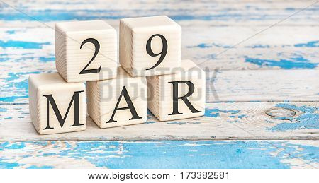 March 29th. Wooden cubes with date of 29 March on old blue wooden background.