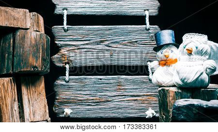 Wedding couple of yarn handmade snowmen. Triple wooden signboard and stack of wood stumps