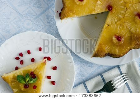 Homemade pineapple upside down cake with a slice of cake and pomegranate seeds on white plate with fork on light cloth napkin